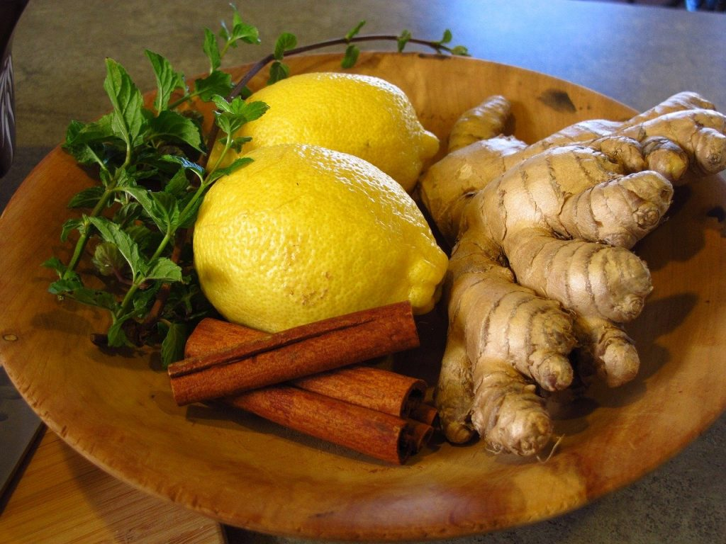 Ginger, lemon, mint, and cinnamon on a plate.