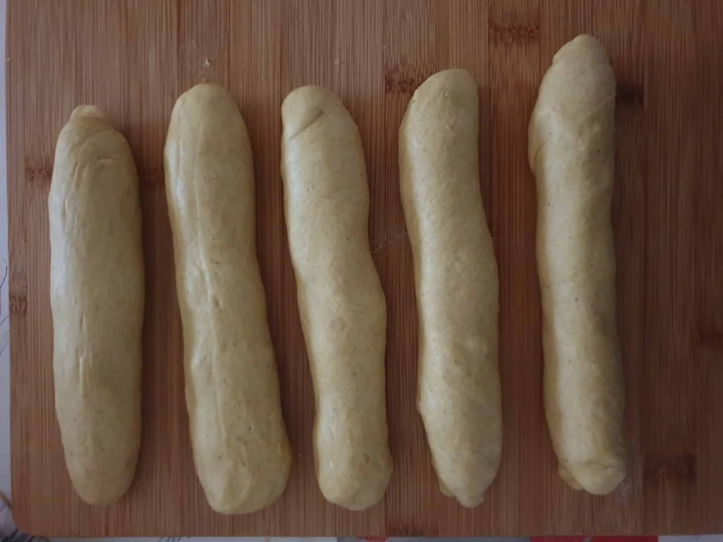Pre-shaped bread sausages before shaping them